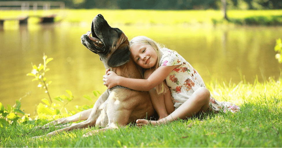 Girl Hugging Dog by a Lake