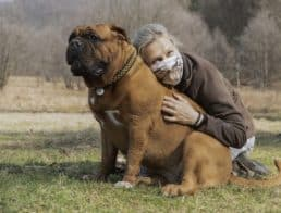 Woman wearing a mask cuddling with a dog