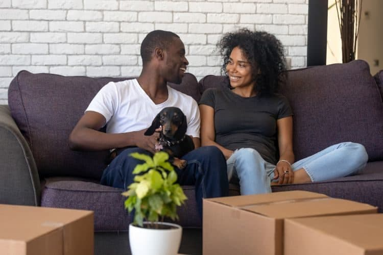 A young couple with their dog surrounded by boxes preparing for their house move